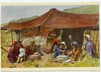 Fotografie Beduinenzelt mit mit Frauen am Mahlstein (Handmühle)