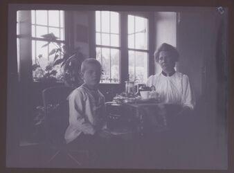 GDIn00236; Planfilmnegativ; [Frau mit Jungen an Tisch sitzend], gehört zum Umschlag [1.32]